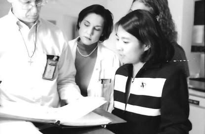 1 man and 3 women, all doctors, stand looking at a medical chart, black and white image.