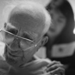 Close up of older man with glasses and nasal oxygen cannula, a female doctor standing examining him in background
