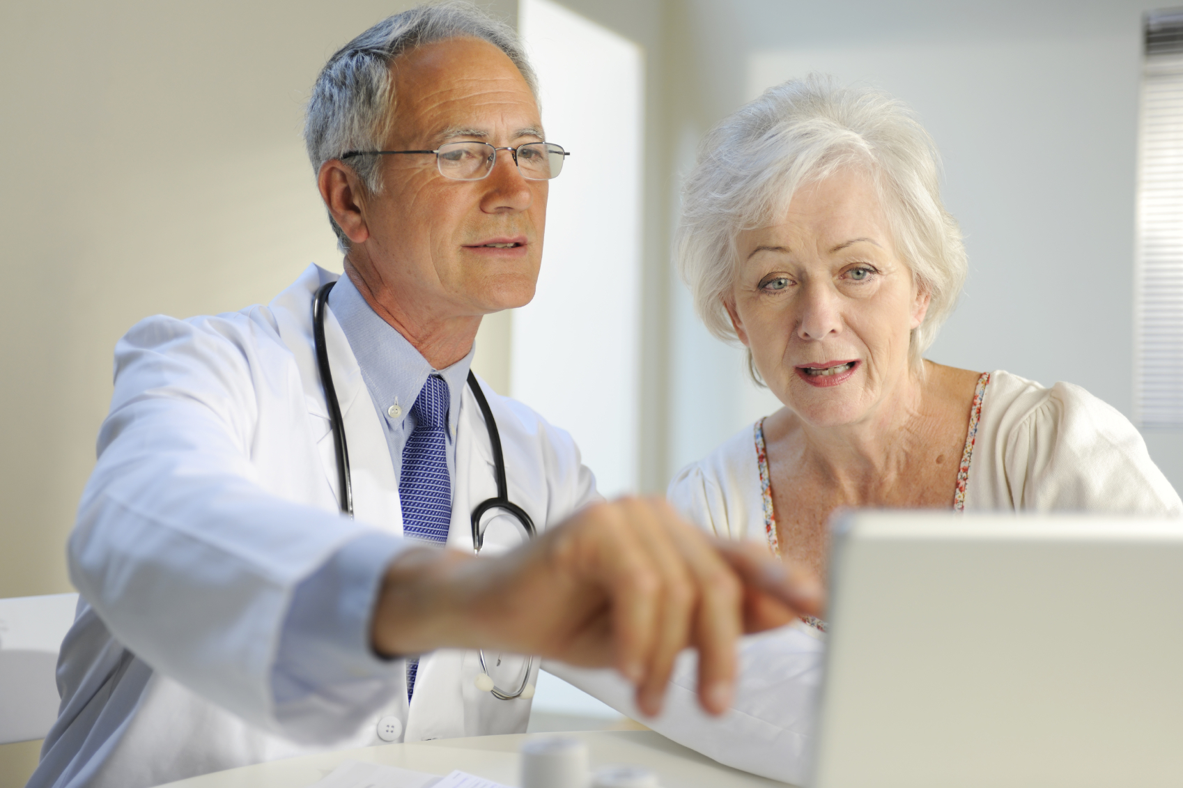 White male doctor and older white female patient look at a computer screen