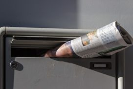 Folded newspaper sticking out of mailbox