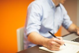 Man sits at desk holding pen and writing in notebook