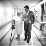 An older woman walking down a hospital hallway with a doctor