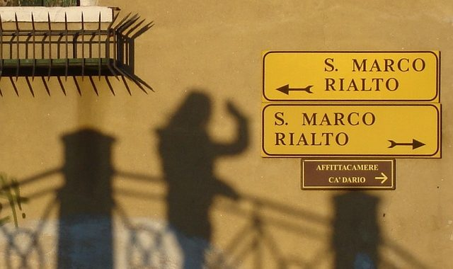 "One street sign pointing left reads ""S. Marco Rialto"", below it another street sign reading ""S. Marco Rialto"" points to the right."
