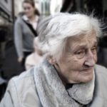 Older woman with white hair and gray coat outside looking to left of camera