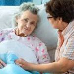 Older woman in hospital bed with younger woman sitting next to her