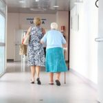 View from behind of older woman walking with cane down hospital hallway, with middle-aged woman beside her.