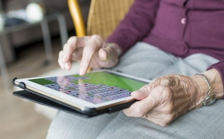 Older woman playing solitaire on an ipad, face is not visible.