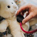 Hand holding stethoscope on a teddy bear's chest