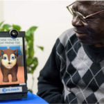 Seated older man looking at iPad with care.coach dog avatar on screen